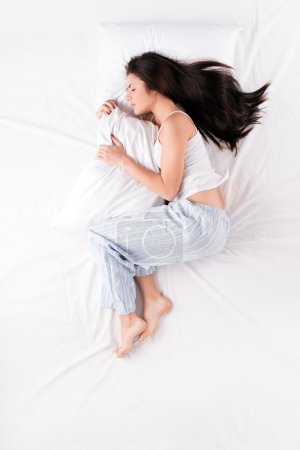 Photo pour Beautiful young woman sleeping in fetal position and holding pillow - image libre de droit