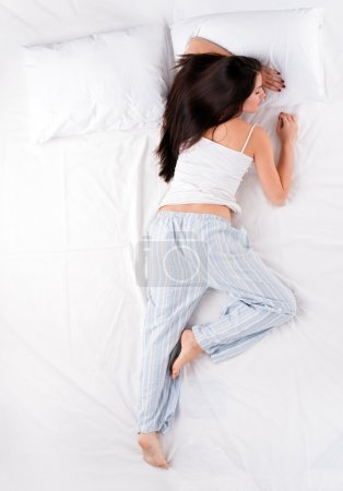 Photo for Beautiful young woman sleeping in starfish position on white bed - Royalty Free Image