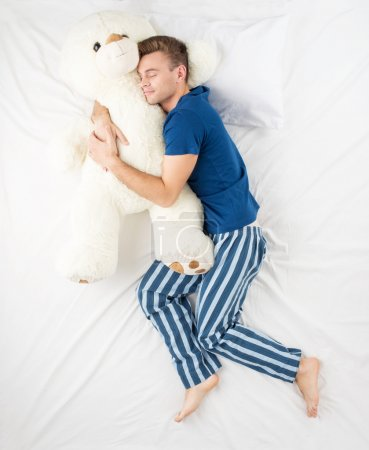 Photo for Young man sleeping in an embrace with a large white teddy bear. Top view photo - Royalty Free Image