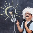 Cheerful boy with fake mustage and Einstein  wig point on bulb visualised on the blackboerd
