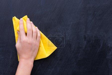 Photo pour Main avec chiffon jaune effaçant quelque chose du tableau noir - image libre de droit