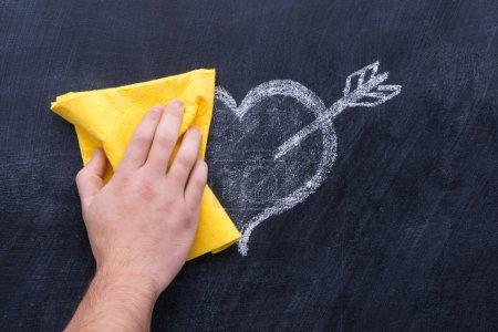Photo pour Main avec chiffon jaune effaçant coeur de dessin du tableau noir - image libre de droit