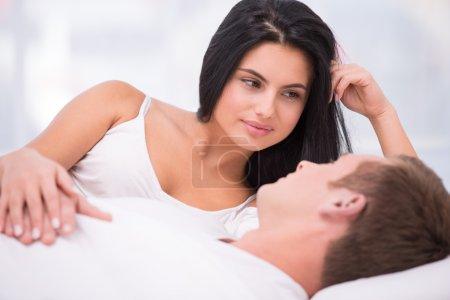 Photo pour Jeune couple couché dans un lit blanc tôt le matin. Belle femme regardant son mari endormi - image libre de droit