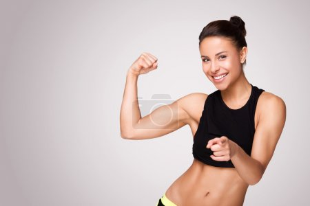 Photo for Cheerfully smiling mixed race sporty woman demonstrating biceps, isolated on white background - Royalty Free Image