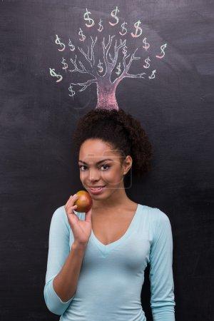 Photo pour Photo d'une jeune femme afro-américaine sur fond de tableau. Femme regardant caméra et tenant pomme près d'arbre dollar peint sur tableau - image libre de droit