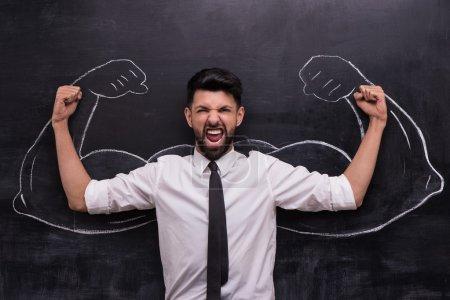 Foto de Divertido cuadro de joven empresario listo para ganar en el fondo de pizarra. Dos fuertes brazos musculares pintados sobre pizarra - Imagen libre de derechos