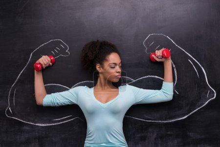 Afroamerikanerin mit Hanteln und bemalten muskulösen Armen auf Kreidetafel