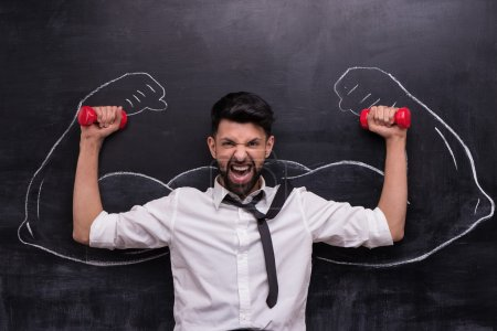 Funny picture of young businessman with dumbbells ...