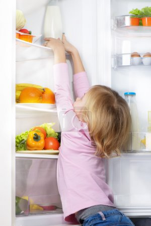 Little cute girl trying to pick food from fridge