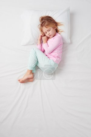 Photo for Top view photo of little girl sleeping on white bed. Quiet Foetus pose. Concept of sleeping poses - Royalty Free Image