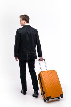 Photo pour Photo de dos de jeune homme d'affaires portant un costume et marchant avec une valise orange. Isolé sur fond blanc - image libre de droit