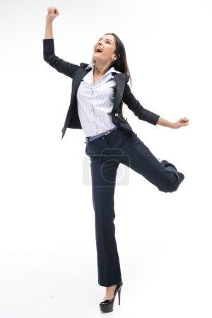 Photo pour Photo d'une jeune femme d'affaires prospère portant un costume. Elle sourit joyeusement et se réjouit. Isolé sur fond blanc - image libre de droit