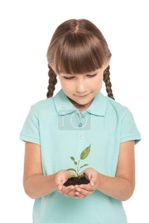 Photo pour Petite fille mignonne avec deux tresses est isolé sur fond blanc. Fille souriant, tenant le germe vert dans les mains et le regardant - image libre de droit