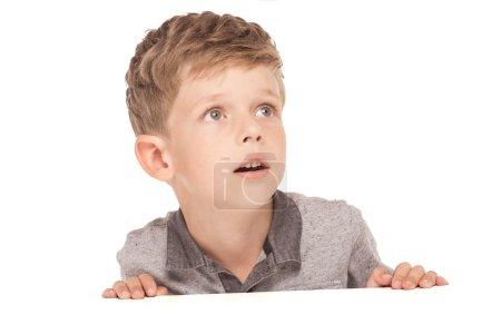 Photo pour Mignon petit garçon est isolé sur fond blanc. Garçon regarder de côté dans la surprise - image libre de droit