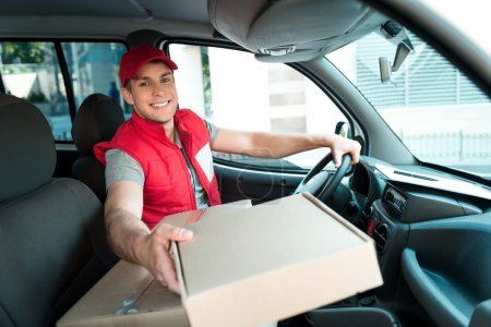 Photo for Colorful picture of courier delivers package. Man is sitting in the car, looking at camera and smiling - Royalty Free Image