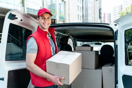 Photo for Colorful picture of courier delivers package. Courier holding the box and smiling - Royalty Free Image