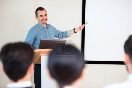 Photo for Photo of handsome young businessman making presentation with whiteboard on seminar or meeting to business people - Royalty Free Image
