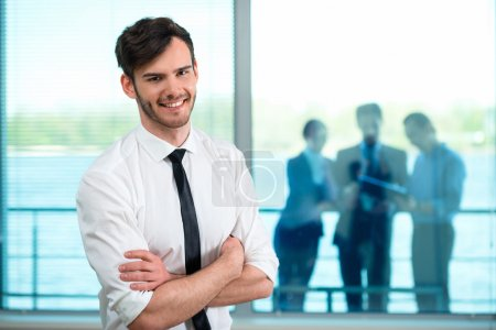 Photo for Portrait of handsome young businessman looking at camera. Office interior. Business people on background - Royalty Free Image