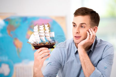Photo for Photo of male tourist. Young man looking at small ship thoughtfully and dreamily. Travel agency office interior with big world map - Royalty Free Image