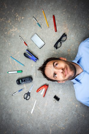 Photo for Top view funny photo of businessman with beard wearing shirt. Businessman thoughtfully looking up and lying on floor full of office supplies - Royalty Free Image