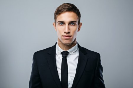 Foto de Portrait of handsome young businessman standing on grey background. Businessman wearing suit and tie, and seriously looking at camera - Imagen libre de derechos
