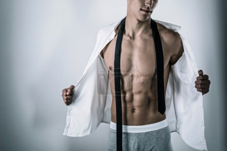 Photo for Studio portrait of handsome sexy sporty young man. Muscular man with naked torso wearing grey underwear, white shirt and tie - Royalty Free Image