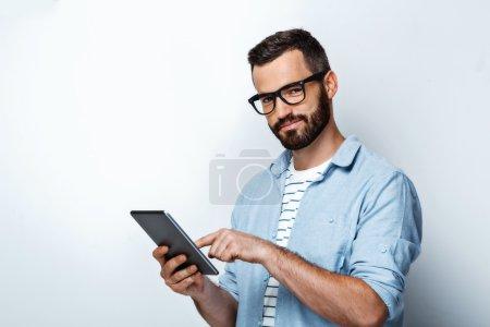 Photo pour Jeune homme élégant avec barbe sur fond blanc. Beau homme portant des lunettes, utilisant un ordinateur tablette et regardant la caméra - image libre de droit