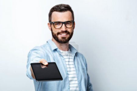 Photo for Young stylish man with beard on white background. Handsome man wearing glasses, smiling, showing tablet computer and looking at camera - Royalty Free Image