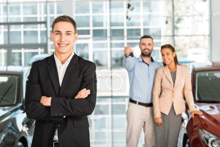 Photo pour Photo de jeunes hommes consultant et acheteurs avec des clés dans le salon de l'automobile. Concept de location de voiture - image libre de droit