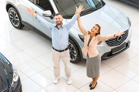 Photo pour Photo de vue supérieure de jeune couple heureux après affaire réussie dans l'exposition automatique. Concept pour la location de voiture - image libre de droit
