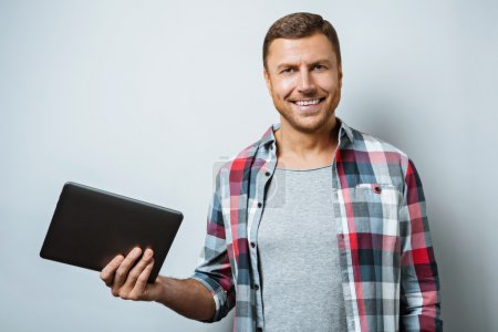 Photo for Studio shot of handsome young man on grey background. Man smiling and holding tablet computer - Royalty Free Image