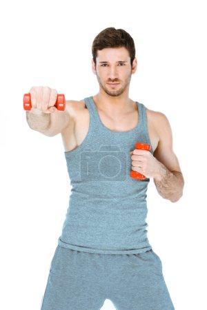 Photo pour Photo de l'athlète musculaire beau sur le fond blanc. Jeune homme utilisant l'uniforme de sports tout en s'entraînant avec des haltères - image libre de droit