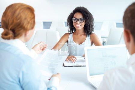 Photo pour Jeune belle femme africaine ayant une entrevue ou une réunion d'affaires avec les employeurs. Employeurs examinant son CV et utilisant un ordinateur portable. Intérieur de bureau moderne blanc - image libre de droit