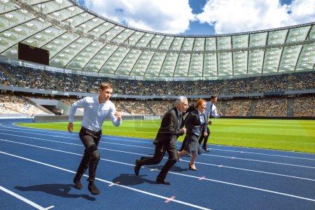 Photo pour Vue de côté photo de confiants hommes d'affaires multiethniques courir pour gagner et traverser la ligne d'arrivée sur la piste de sport moderne. Stade comme fond - image libre de droit