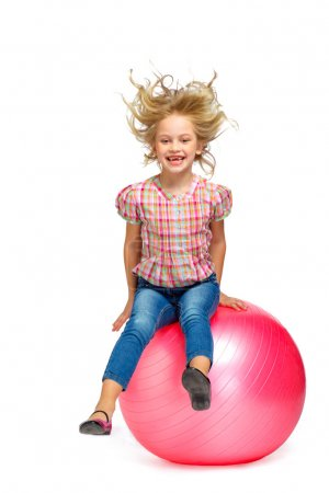 Little girl sitting on pink ball