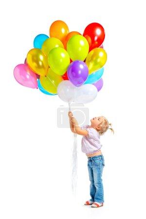 Photo pour Photo colorée de belle petite fille tenant un tas de ballons sur fond blanc. Fille souriant et regardant des ballons - image libre de droit