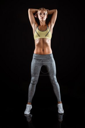 Photo for Young beautiful sporty blonde on black background. Fit sportswoman stretching - Royalty Free Image