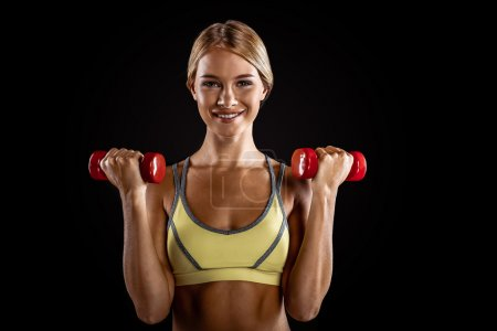 Photo for Young beautiful sporty blonde on black background. Fit sportswoman exercising with red dumbbells - Royalty Free Image