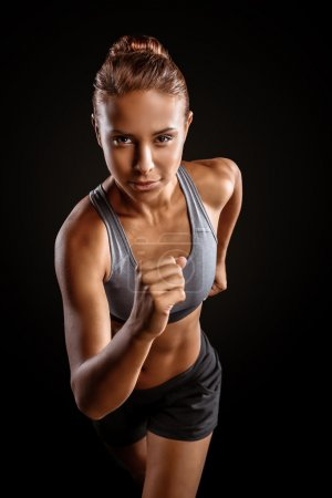Photo for Young beautiful mixed race sportswoman on black background. Fit sporty woman running - Royalty Free Image
