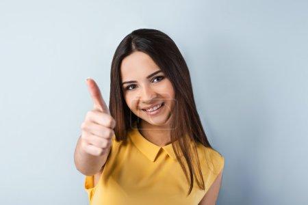 Photo pour Photo de la belle jeune femme d'affaires restant près du fond gris. Femme avec la chemise jaune regardant l'appareil-photo, souriant et affichant le pouce vers le haut - image libre de droit