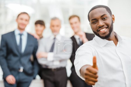 Photo for Photo of young businessman and his colleagues. Businessmen and business woman working in office with big window. Men and woman smiling and looking at camera. African businessman showing thumb up - Royalty Free Image