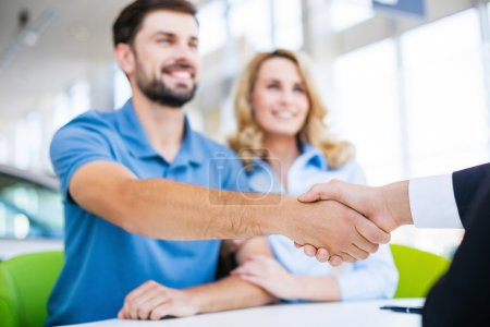 Photo for Photo of young male consultant and couple. Young woman and man buying new car in auto show. Signing of contract and shaking hands. Concept for car rental - Royalty Free Image