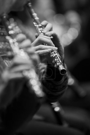 Flute in the hands of a musician in the orchestra closeup