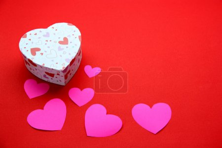 Photo pour Ours en peluche, boîte de chocolats et de coeurs roses avec ruban sur fond rouge, cadeaux Saint Valentin, bannière publicitaire - image libre de droit
