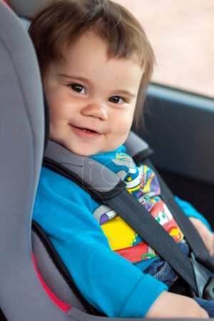 Cute little girl is sitting in her car safety seat