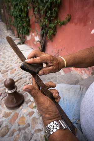 hands of a worker sharpening a rusty machete in Mexico