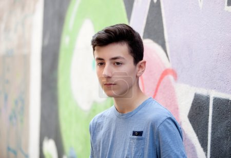 Photo for Portrait of rebellious male teenager near wall with graffiti - Royalty Free Image