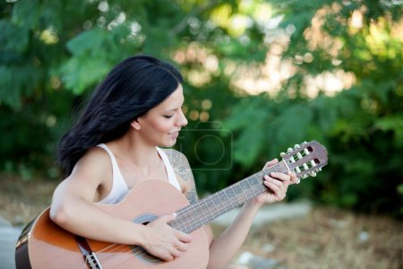 Brunette pretty woman with a guitar