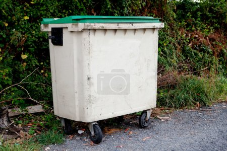 Waste container with green lid