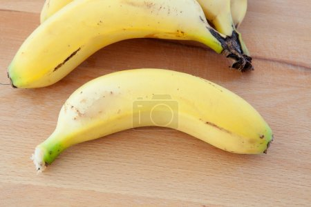 Bananas located on a wooden surface